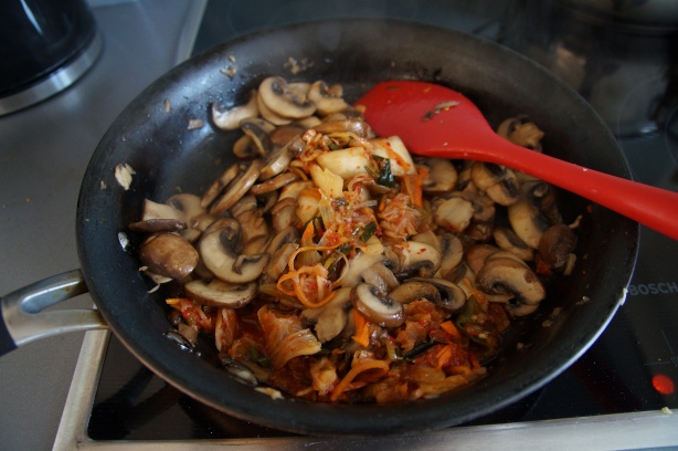 Kimchi and mushrooms in pan